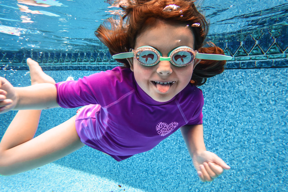 A little girl sticks her tongue out at the camera while swimming underwater.