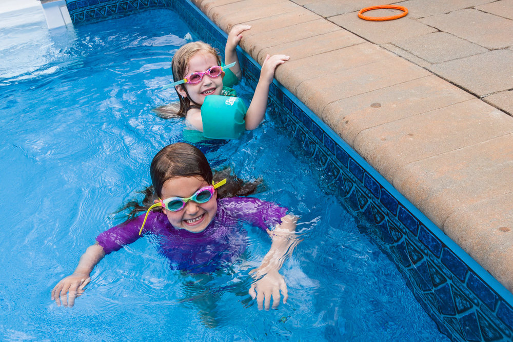 Friends swim in the pool together.