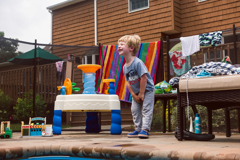 A little boy laughs next to a water table.