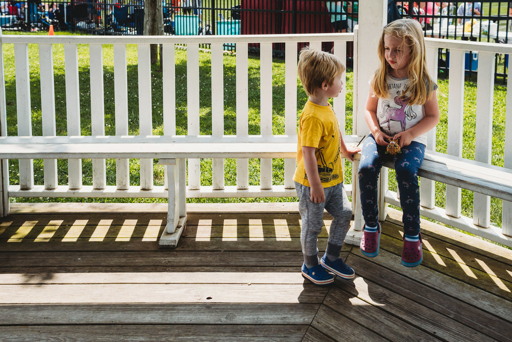 Two kids sit in the shade at the playground.