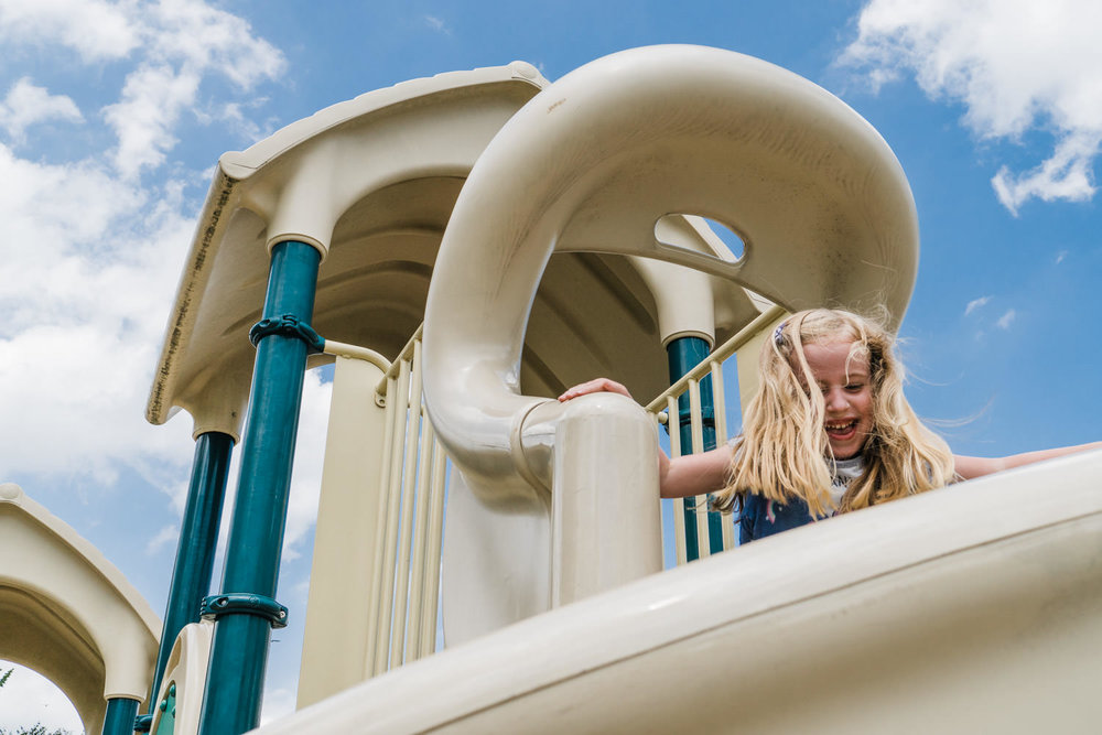 A little girl goes down the slide on a bright sunny day.
