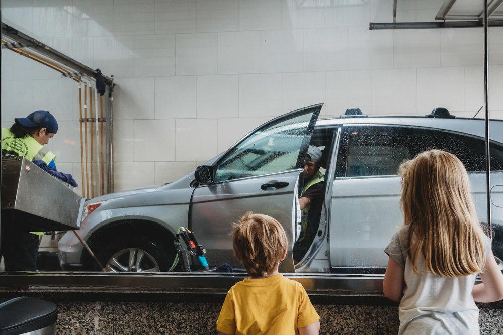 Kids watch their car get washed.