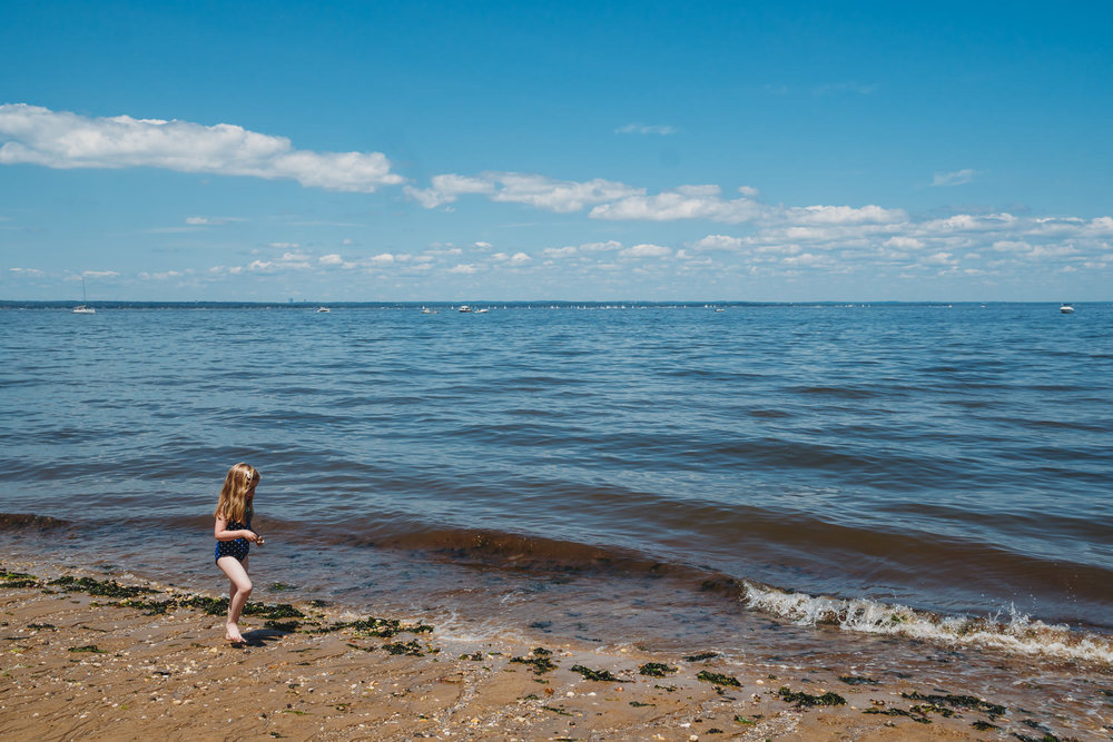 A little girl walks along the beach at Sand Points Preserve.