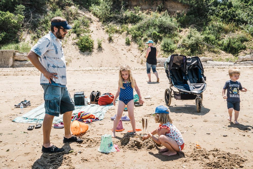 A family collects shells for a sand castle.