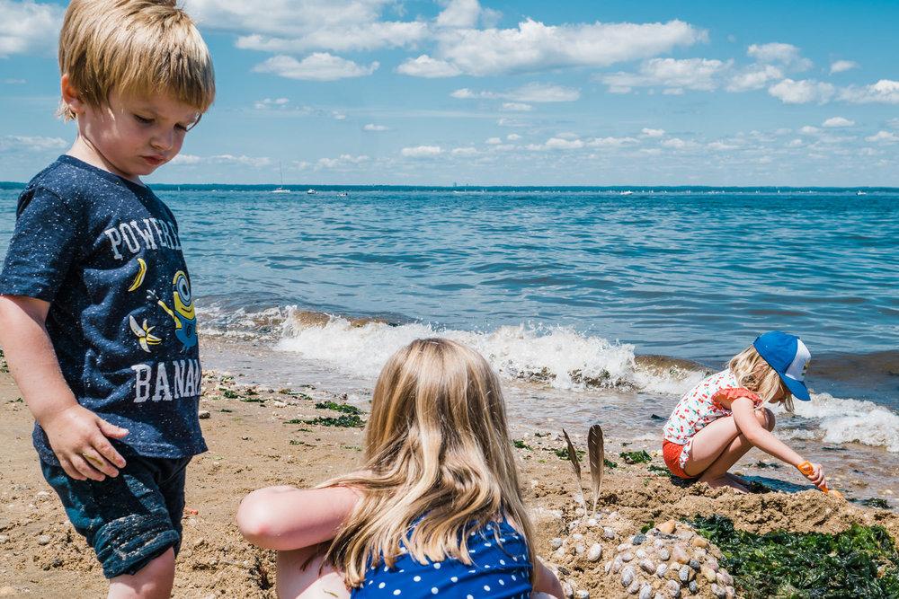 Kids build a sand castle on the beach.