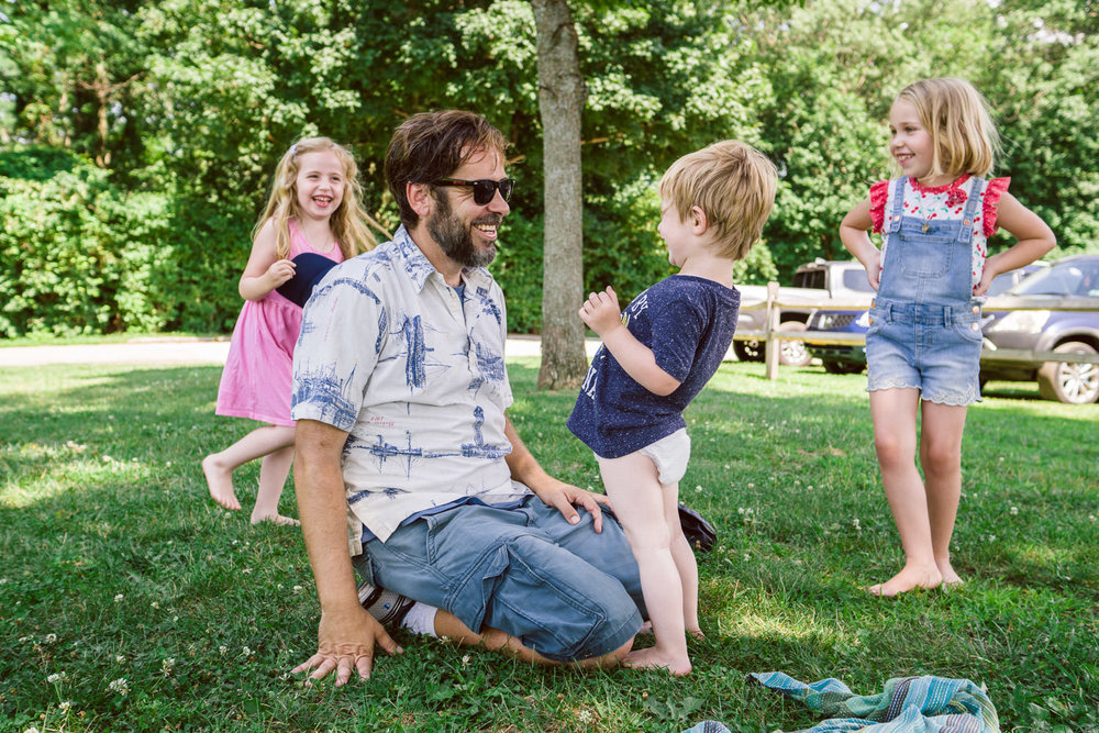 Kids play with uncle on the grass.