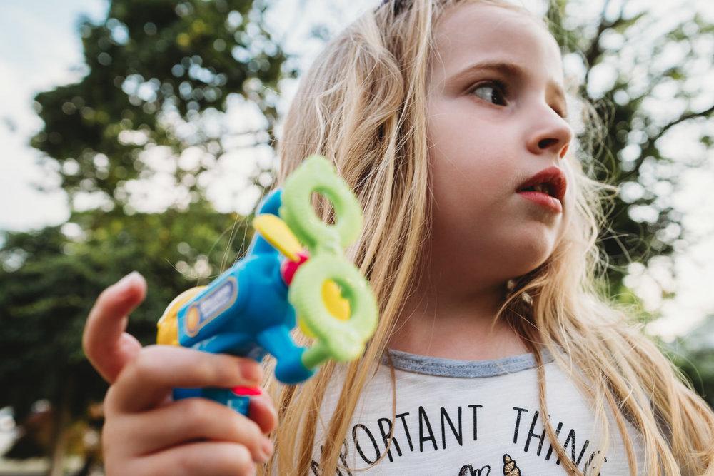 Portrait of a little girl holding a bubble gun.