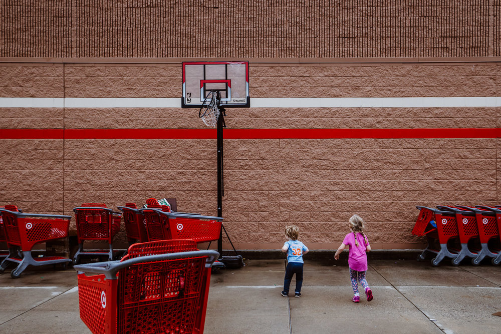Kids jump under basketball hoop outside Target.