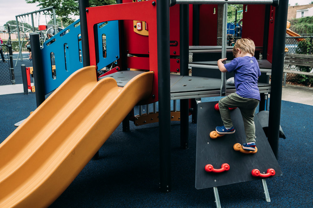 Kids climb a play structure at a playground.