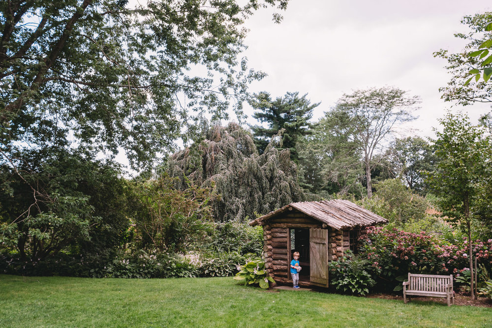 A child stands outside a small shed at Old Westbury Gardens.