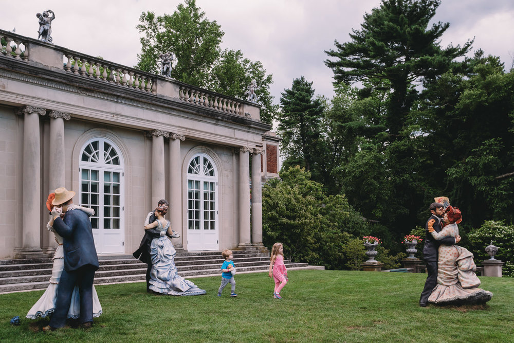 Two kids walk between sculptures in old-fashioned dress at Old Westbury Gardens.