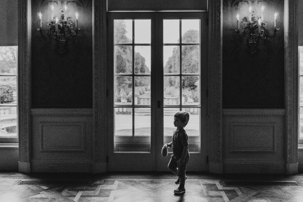 A little boy stands in front of a window inside the house at Old Westbury Gardens.