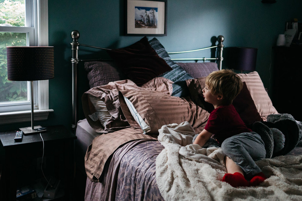 A little boy sits on his parents' bed and looks out a window.