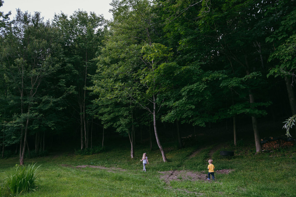 Two kids walk along a path near a wooded area.