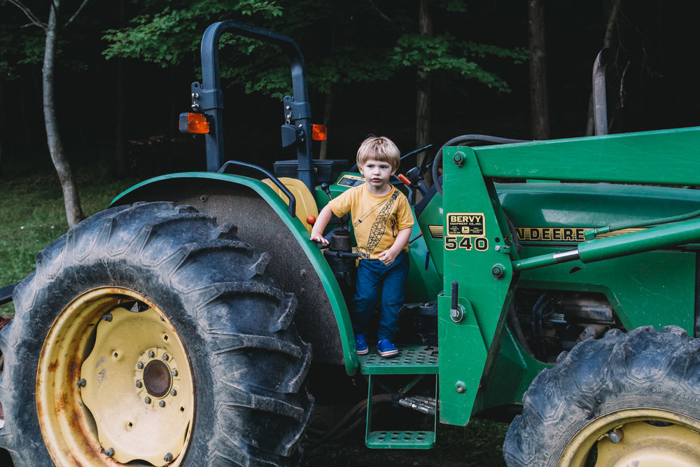 A little boy stands on a tractor.