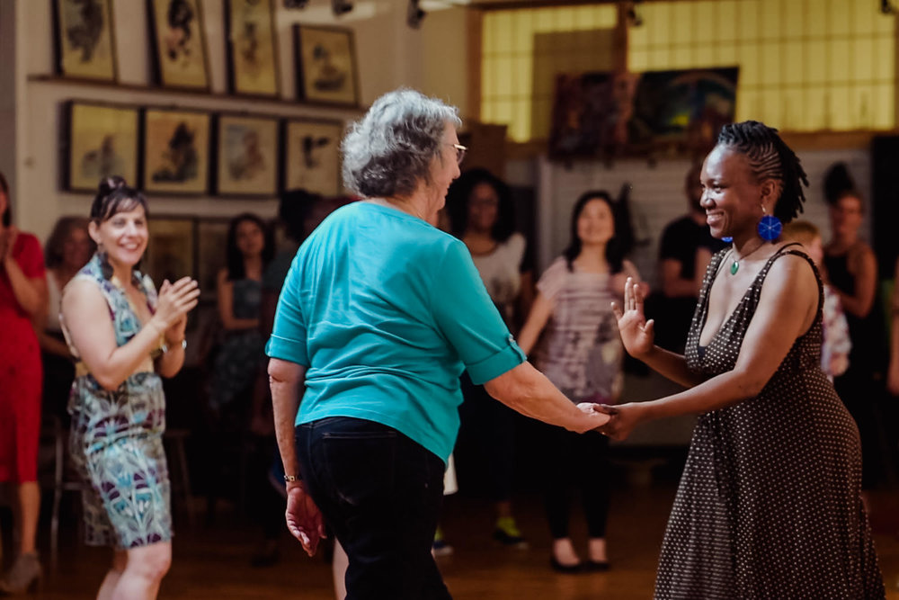 An instructor leads a women to dance at the Project Life Center.