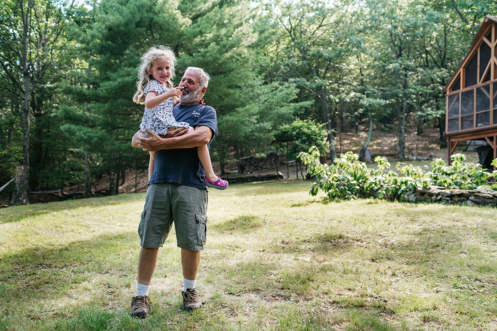 A little girl and her grandfather stand on the lawn in Copake.