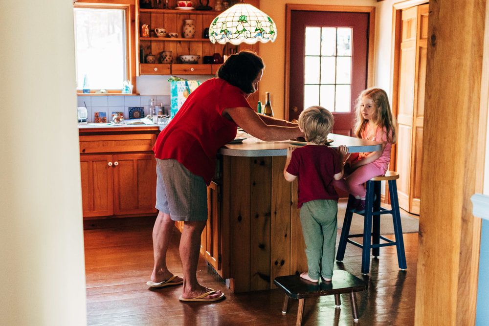 Two kids help their grandmother bake a cake.