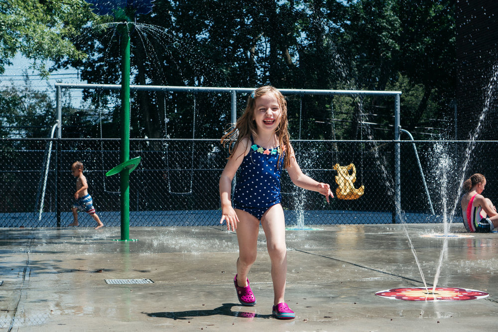 A happy little girl plays in a spray park.