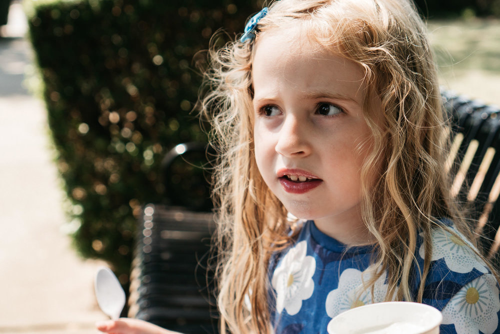 A portrait of a little girl eating ice cream.