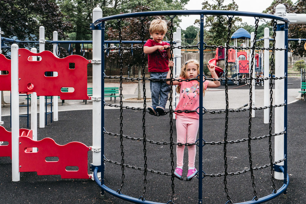 Two kids climb a playground structure at Christopher Morley Park.