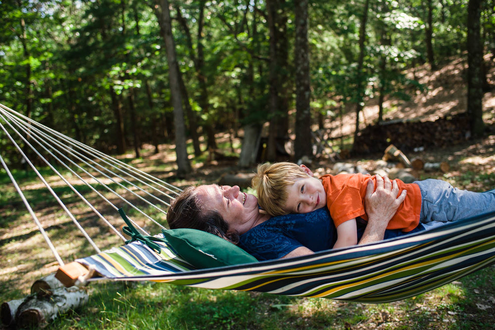 A little boy cuddles with his grandmother on a hammock.