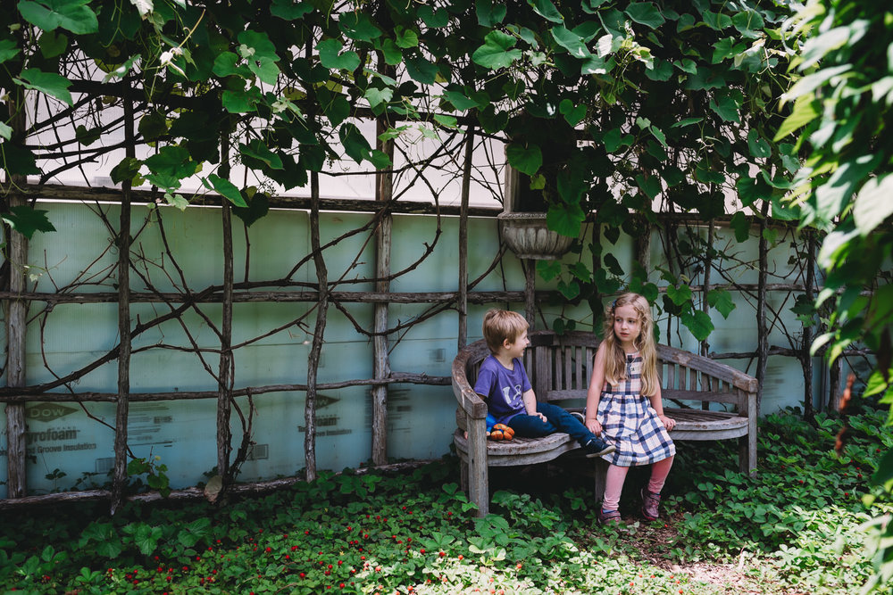 Two children sit on a bench at the Berkshire Botanical Garden.