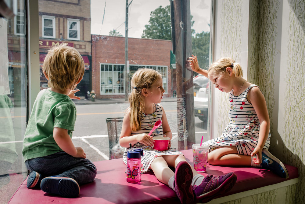 Three children chat in the window of a frozen yogurt shop.