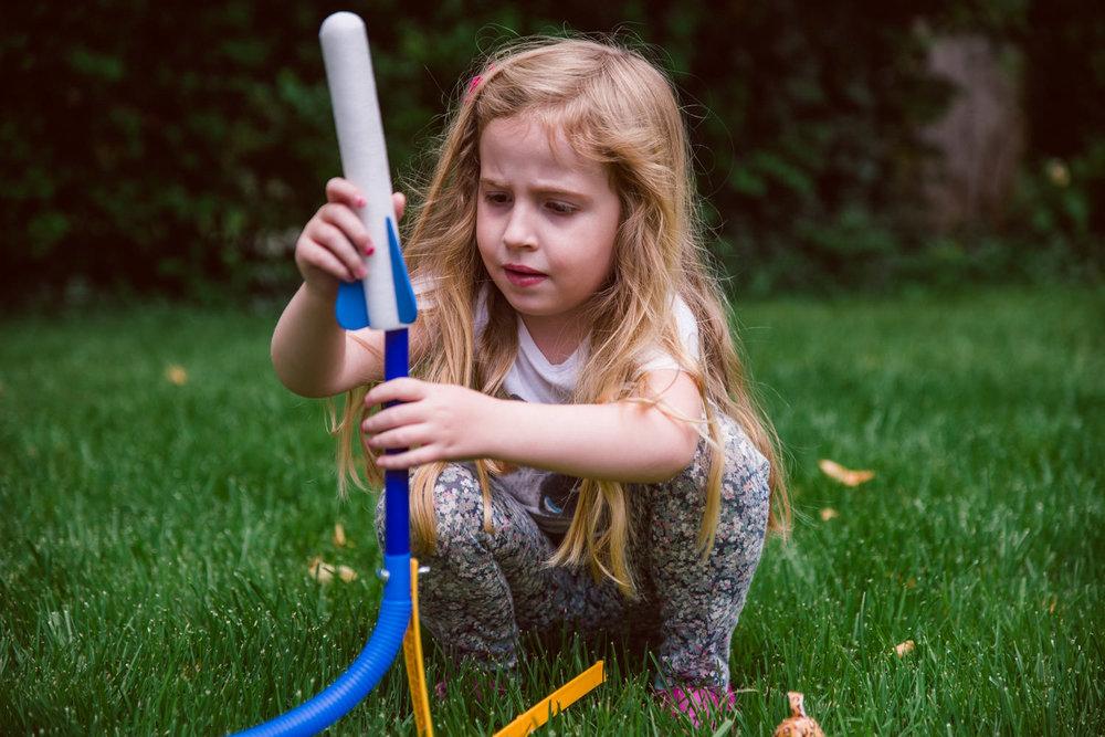 A little girl loads a rocket on her stomp rocket launcher.