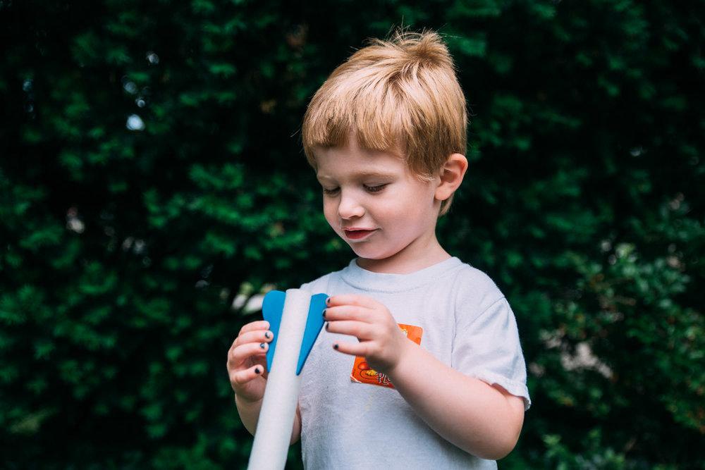 A little boy holds a stomp rocket.