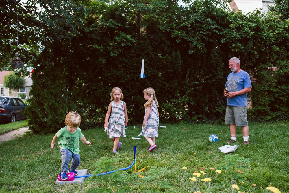 Kids fire off a stomp rocket in their front yard.