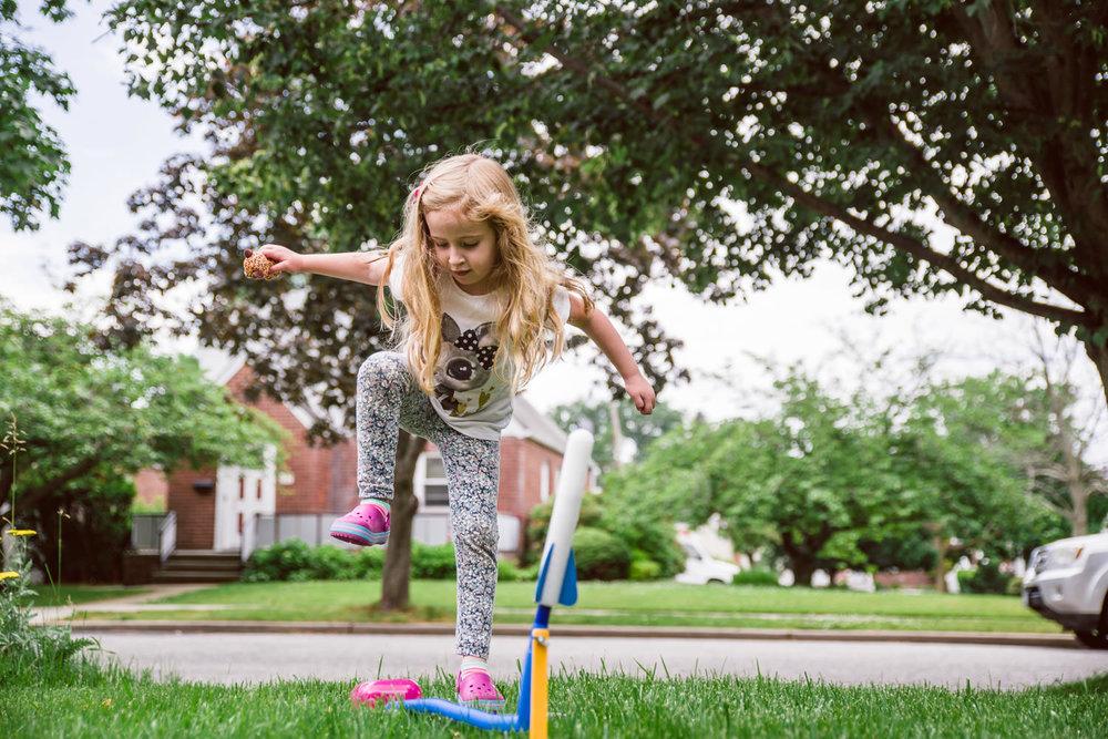 A little girl launches a stomp rocket.