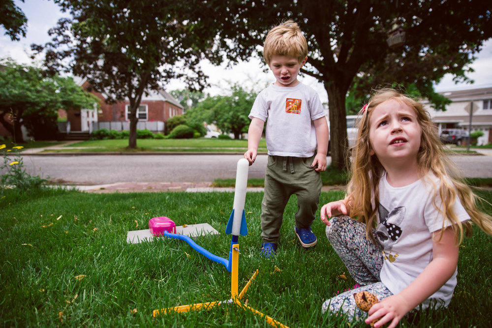 Kids watch a stomp rocket launch.