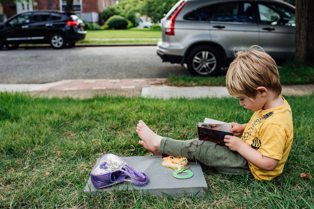 A little boy sits in his front yard.