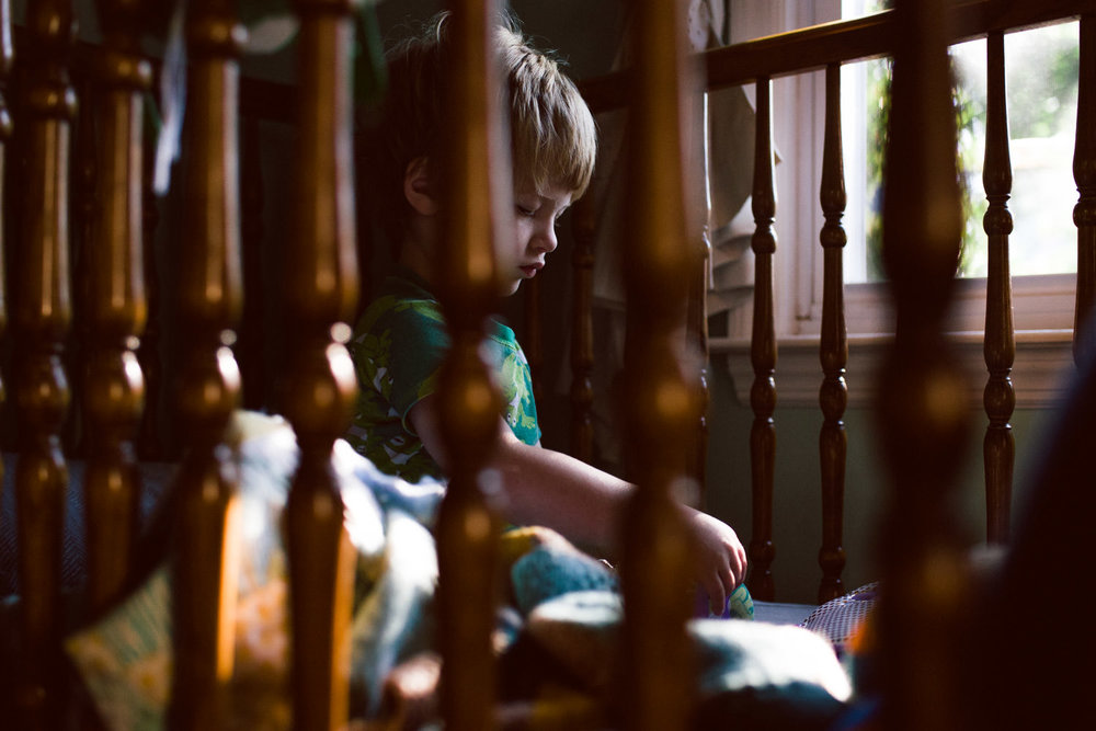 A toddler sits in his crib in the morning light.