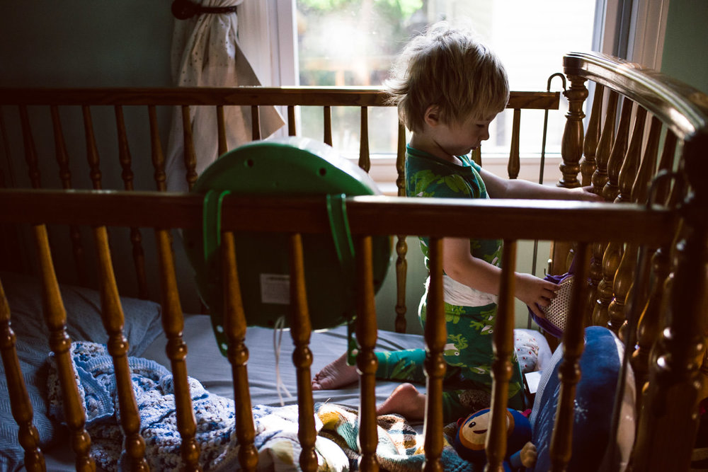 A toddler plays in his crib one morning.
