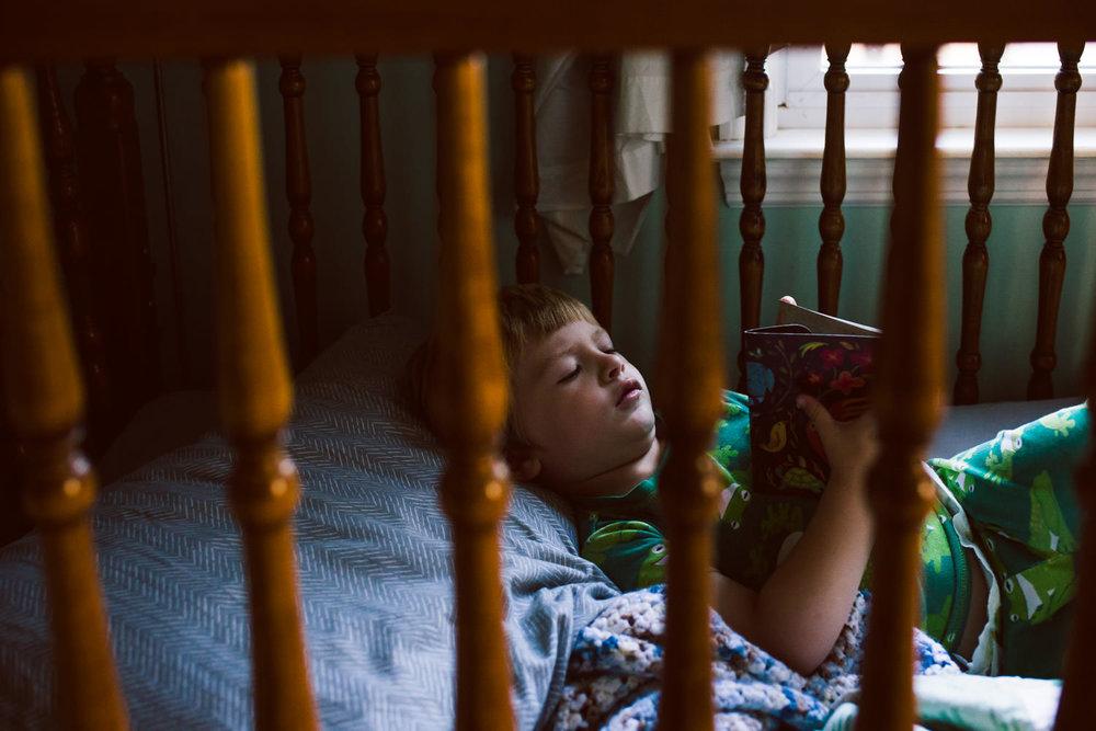 A little boy lies in his crib.