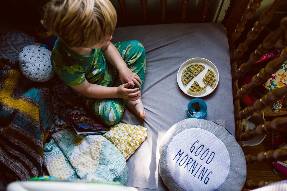 A little boy eats breakfast in his crib.