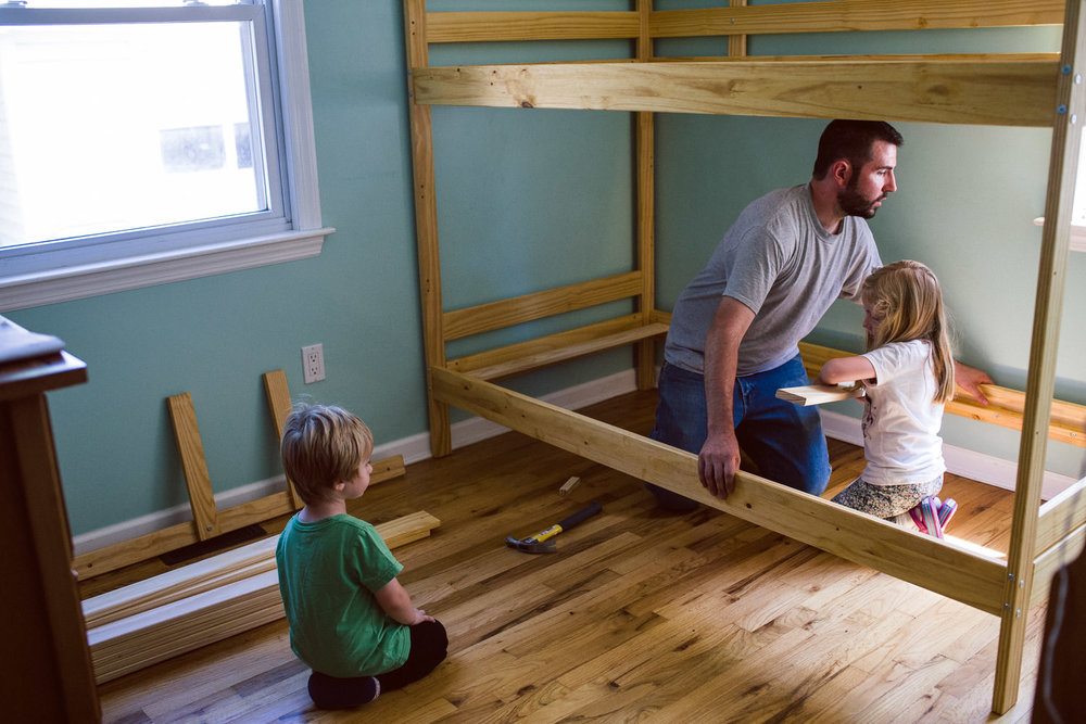 Two kids help their dad build a bunkbed.