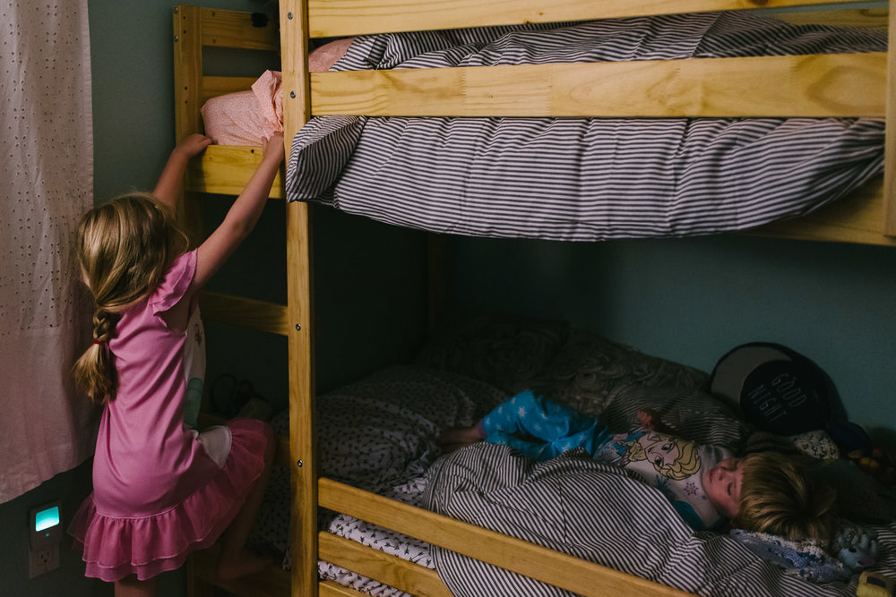 Two kids climb into their bunkbed.