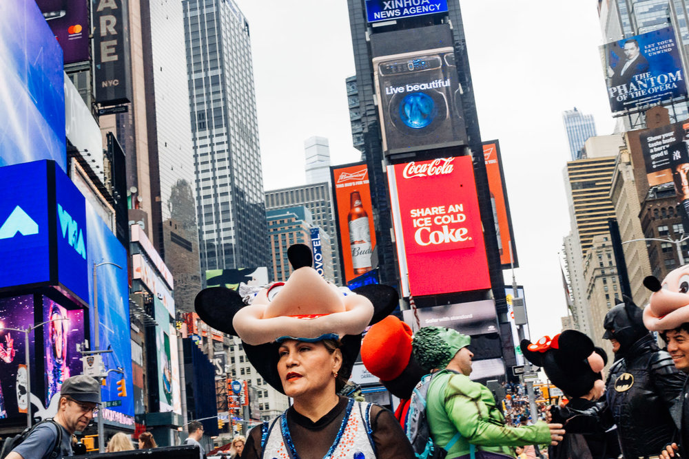 A woman lifts up her Minnie Mouse mask in Times Square.