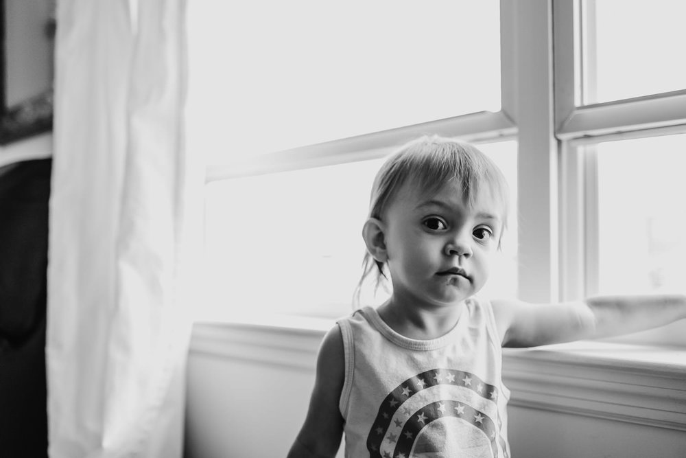 A portrait of a little girl standing next to a window.