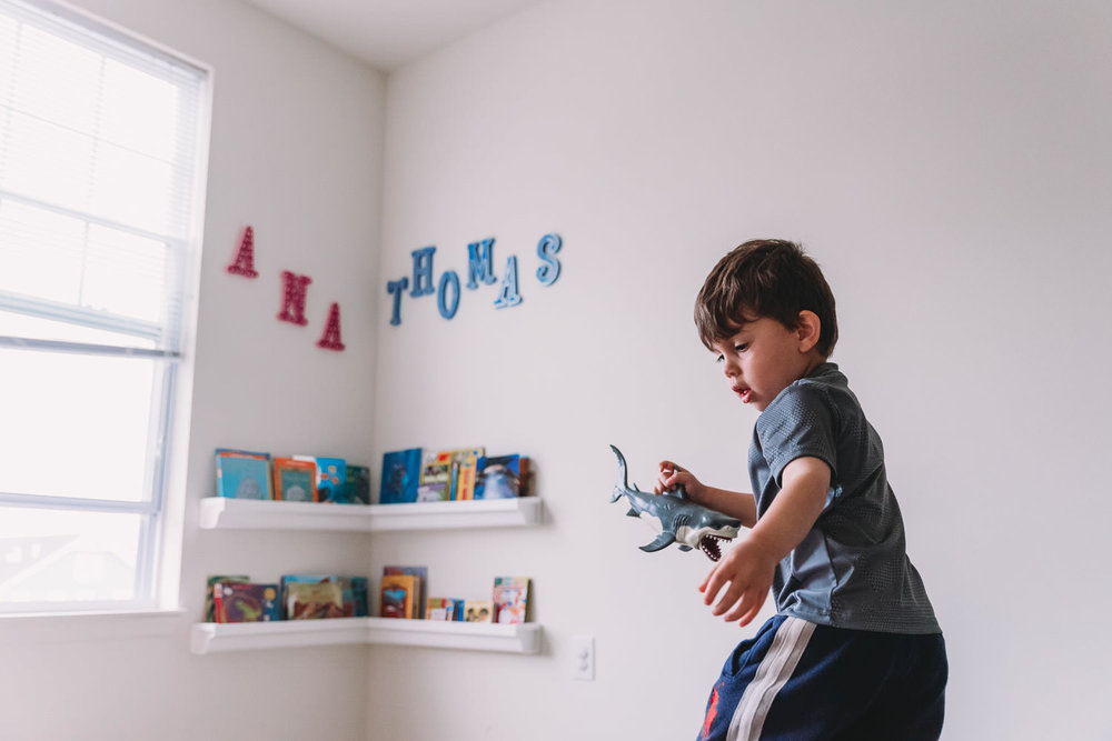 A little boy holds a toy shark in his playroom.