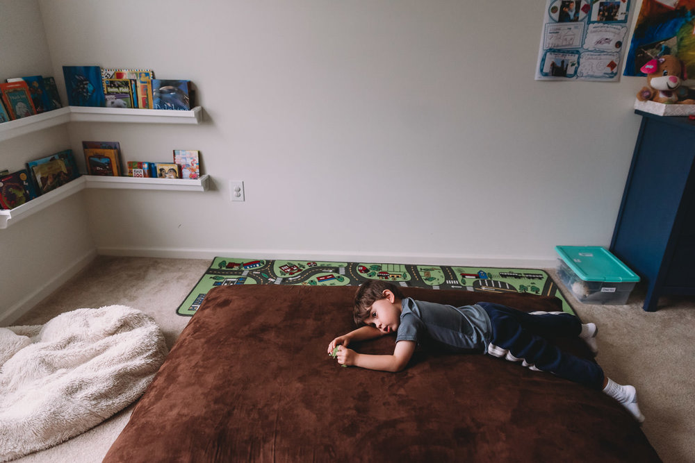 A little boy lies on a beanbag in his playroom.