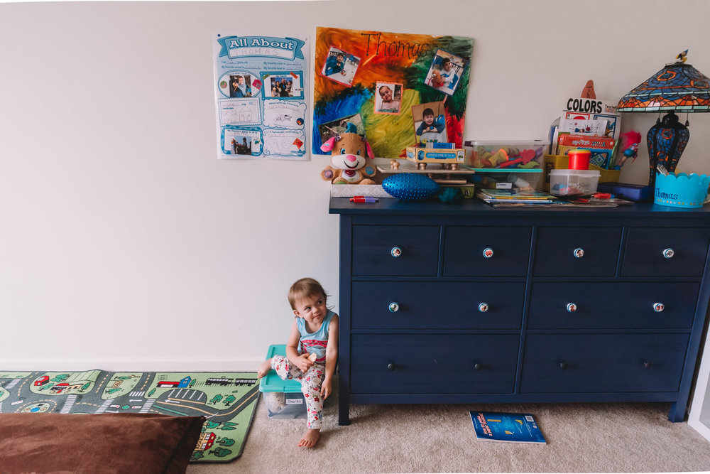 A toddler girl sits next to her dresser.