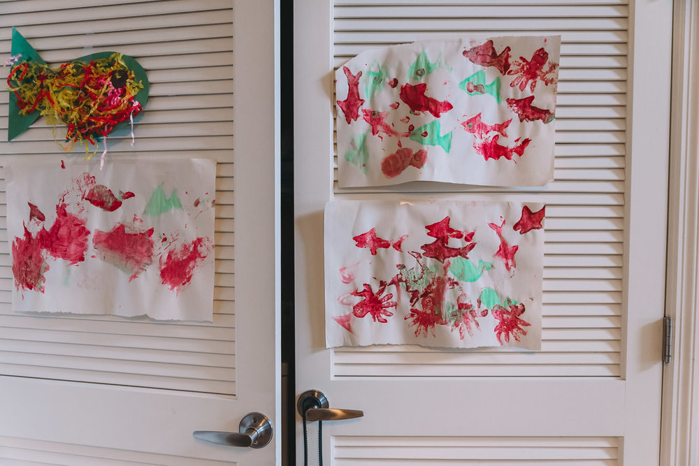 Kids' paintings hung on a closet door.