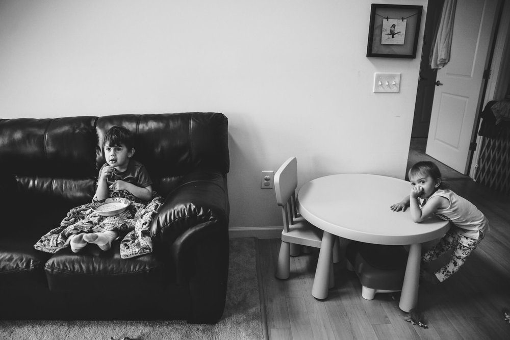 Two kids sit and watch a movie.