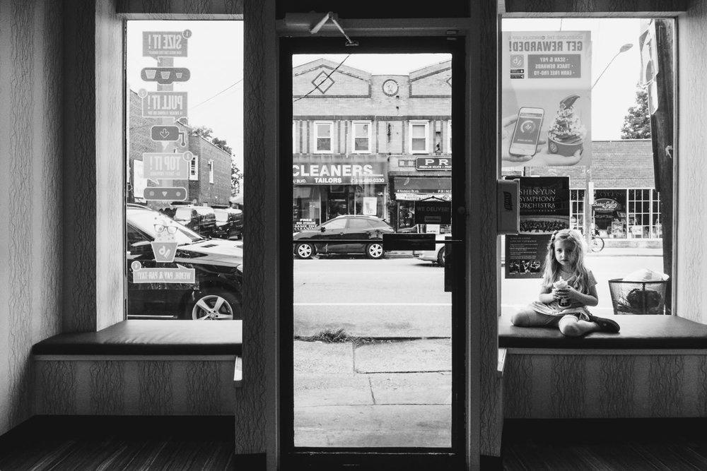 A little girl sits in a window of a yogurt shop.
