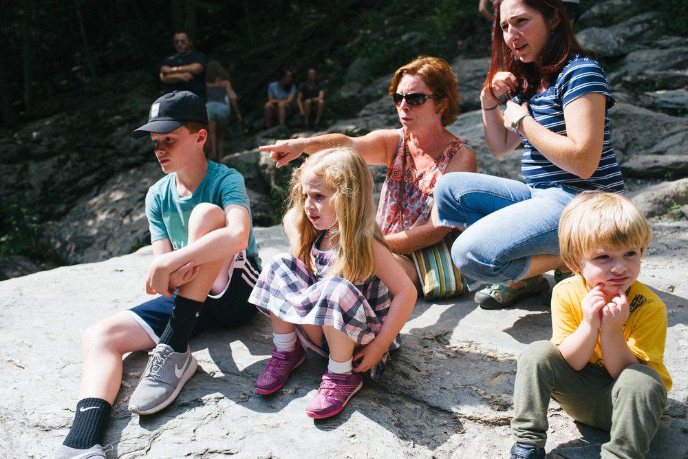 Family members sit and look at Bash Bish Falls.