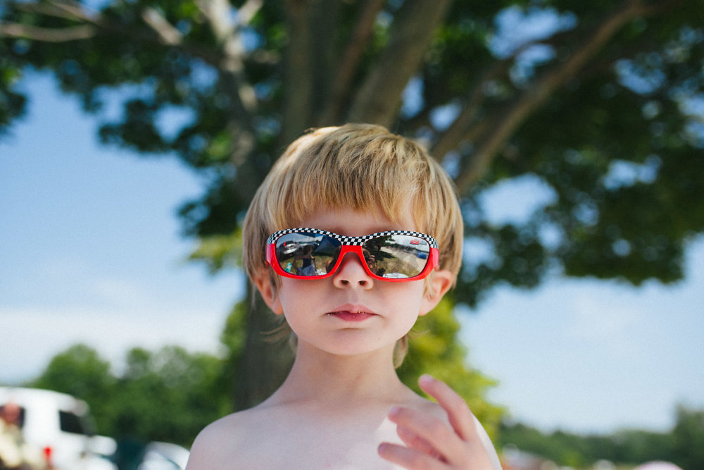 A little boy in red sunglasses.